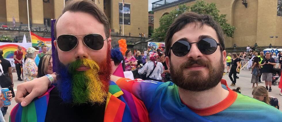 Man med färgglatt skägg brevid man i solglasögon och pridetröja.