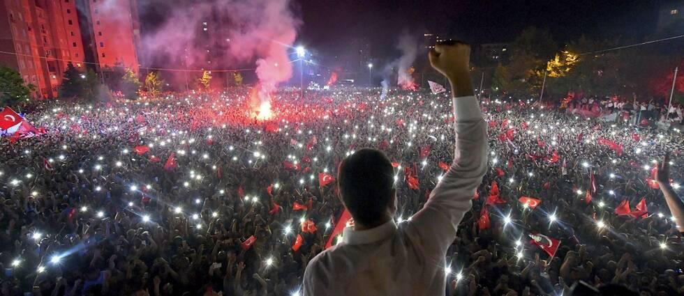 Ekrem Imamoğlu står framför ett folkhav med turkiska flaggor.