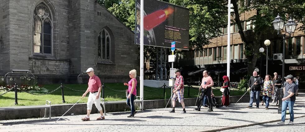 Flera ur Synskadades rikförbund passerar Nicolaikyrkan på Stortoget. De går med käpp, och på rad.