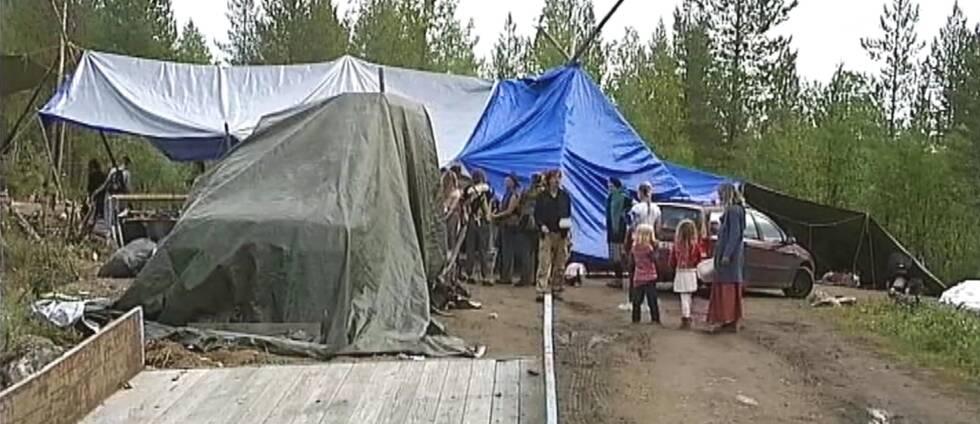 några personer på öppen plats i skogen, presenningar uppspända som tält-tak.