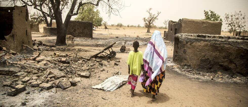 En mor går med sitt barn i ruiner i Mali
