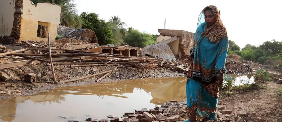 En sudanesisk kvinna i staden Geli, fyra mil norr om huvudstaden Khartoum, kliver runt bland bråte från byggnader som förstörts efter att en kraftig störtflod dragit fram.