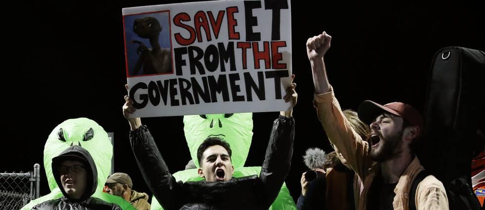 Aktivister i aliendräkter ropar slagord och håller upp ett plakat.
