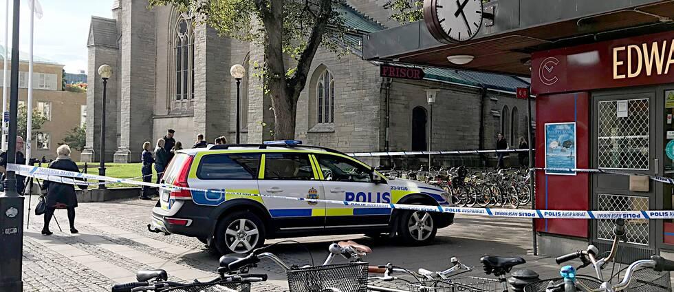 Polisavspärrning och polisbil framför urbutik