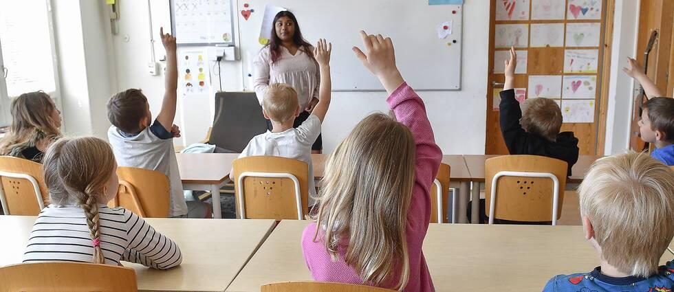 Skolbarn i ett klassrum räcker upp händerna.