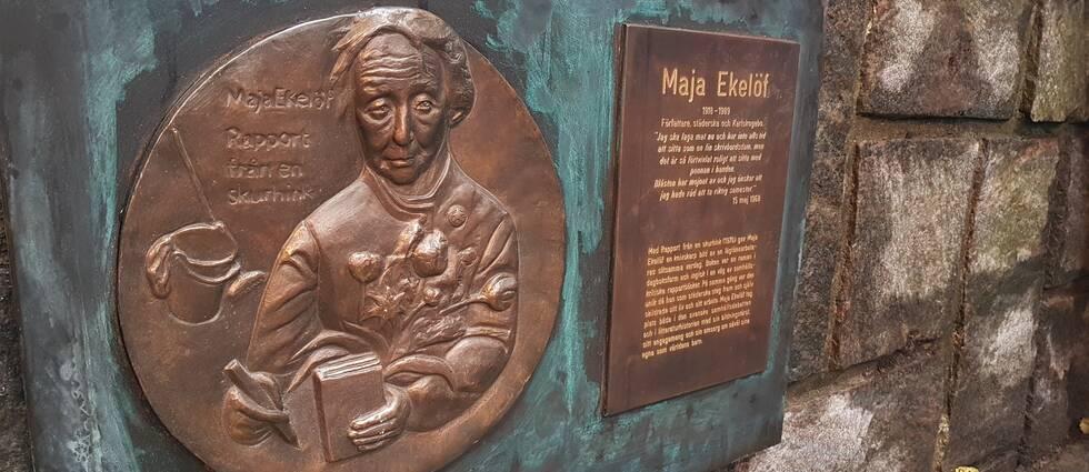 Minnesplakett över Maja Ekelöf sitter på en mur utanför biblioteket i Karlskoga.