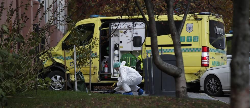 En person undersöker en ambulans.