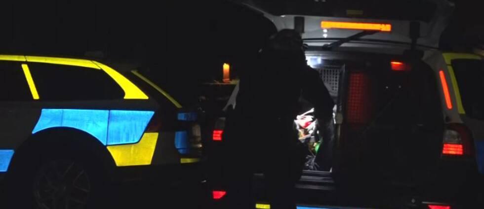 En polis plockar ut saker ur bagageluckan på en polisbil.