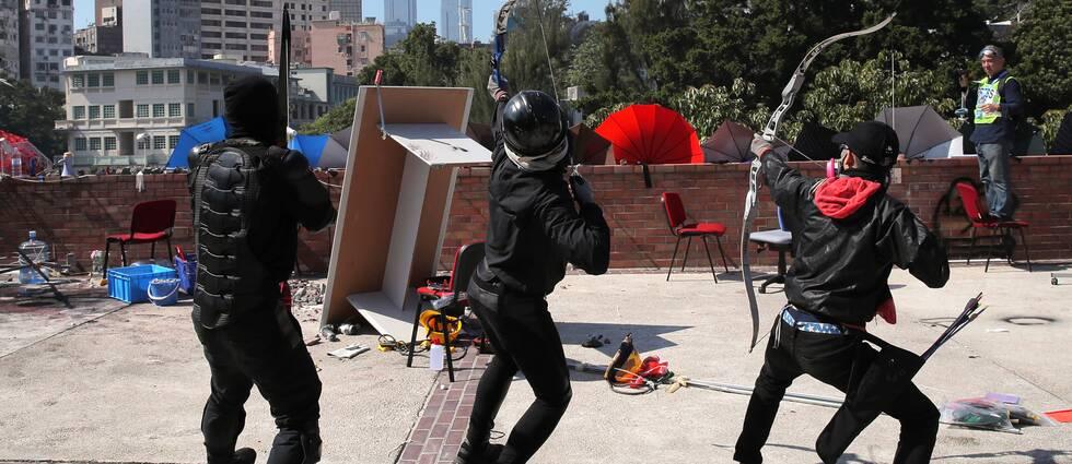 Tre demonstranter skjuter pilar från ett hustak.