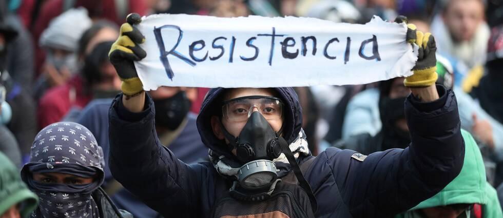 """En demonstrant i Colombia håller upp en skylt som lyder """"motstånd"""" på spanska."""
