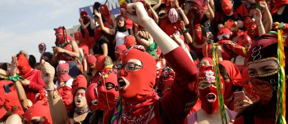 Kvinnor i röda masker protesterar mot kvinnovåld och regeringen i Chile.