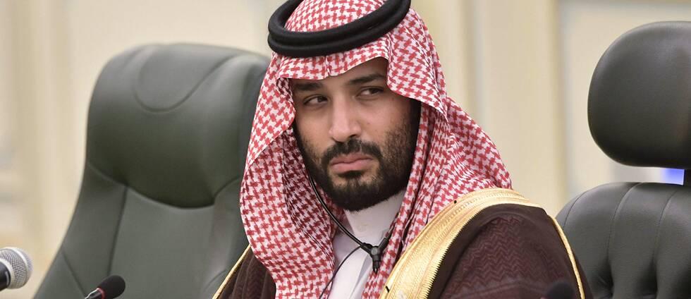 En bild på saudiske kronprinsen i traditionell saudisk klädsel sittandes i ett stol vid ett konferensbord.