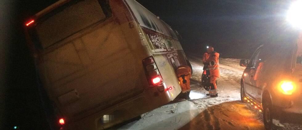 en buss står kraftigt lutande på sidan av snöig väg, räddningspersonal utanför