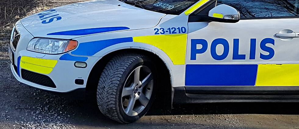 Polisbil på grusväg.