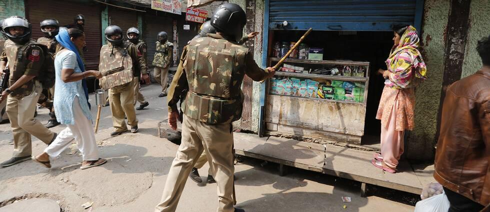 Säkerhetsstyrkor beordrar en kvinna att stänga sin affär i New Dehli under onsdagen. Minst 20 personer har dött till följd av oroligheter i staden.