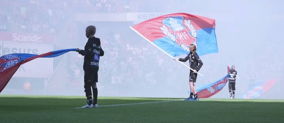 Bild från en fotbollsmatch där ungdomar viftar med flaggor på planen.