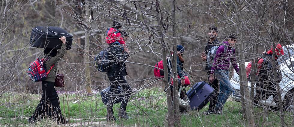 Migranter och flyktingar bär på bagage och försöker ta sig till gränsen mellan Turkiet och Grekland. Arkivbild.