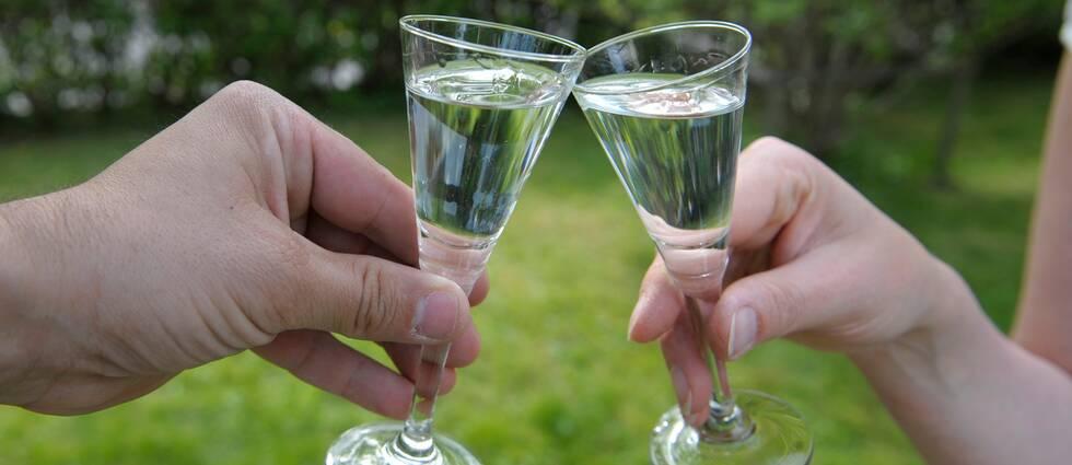 Två personer skålar med sina snapsglas. Temabild.