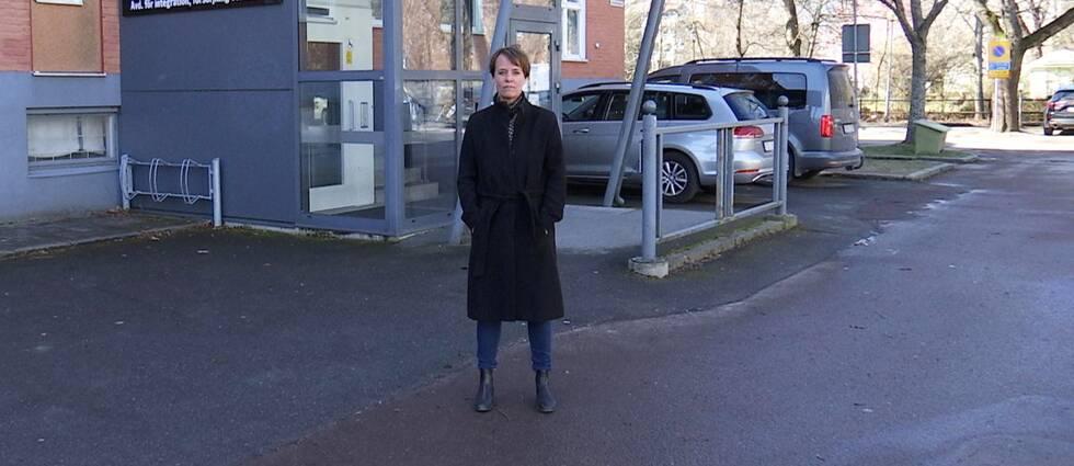 Kvinna i svart kappa står utanför en reception och tittar in i kameran.