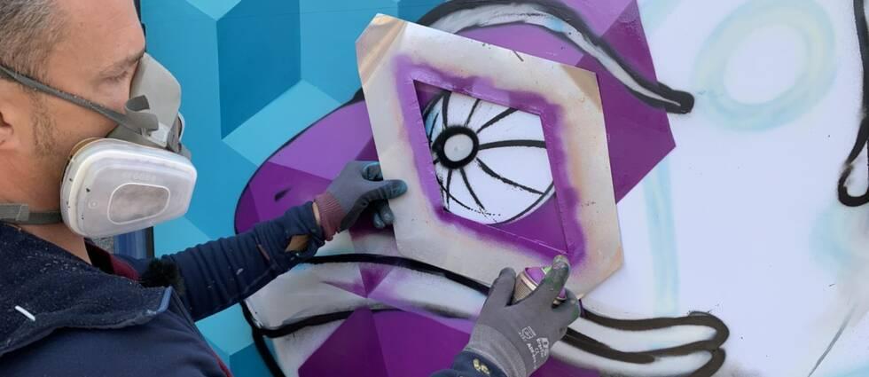 En graffitimålare sprayar en kameleont på ett skyltfönster.