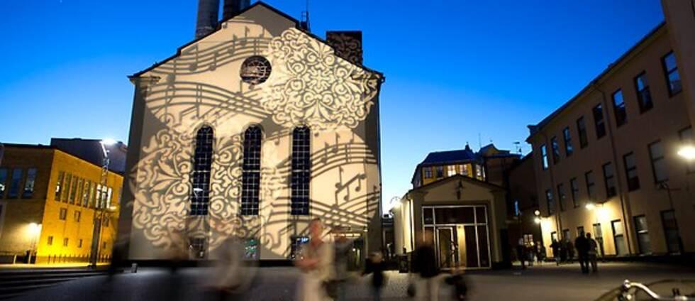 Värmekyrkan i Norrköping under Kulturnatten med ljusspel av ornament och noter.