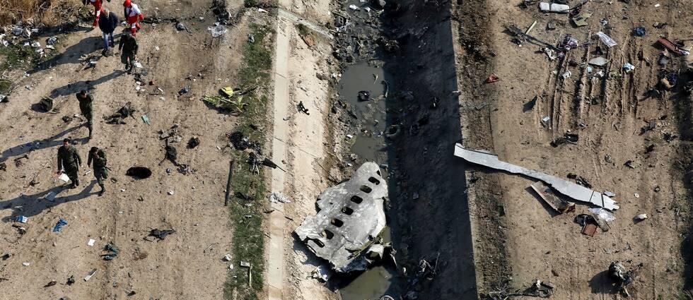 Räddningsarbetare i området där planet kraschade 8 januari i år. Man ser fragment av planbitar spridda över området.