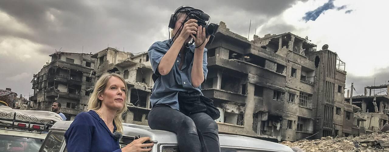 Stina Blomgren och fotograf Pernilla Edholm i en krigshärjad stad. Pernilla sitter på taket på en bil.