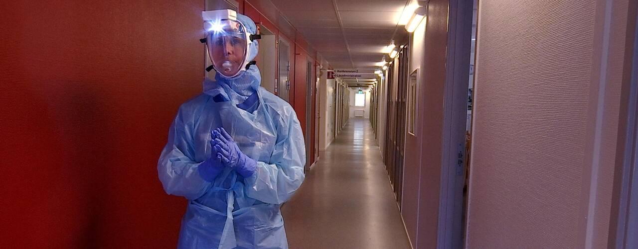 Therese står med blå handskar, blå plastöverdragskläder, blå huva och en mask med genomskinklig plast över ansiktet och ovanför sitter en vit liten dosa som är en fläkt med en liten lampa i. Hon står i en lång korridor.