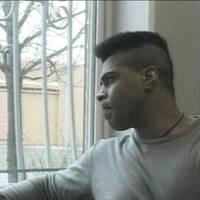 en man tittar ut genom fönster med galler