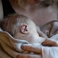 Kvinna med bebis i famnen.