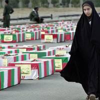 En kvinna i chador passerar kistor svepta i iranska flaggor.