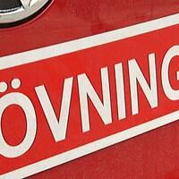 En röd övningskörningsskylt på en röd baklucka.