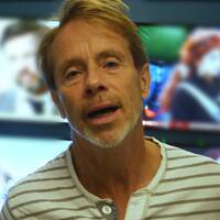 SVT:s sportkommentator Jakob Hård står framför tv-apparater.