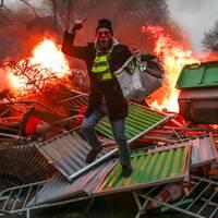 Isabelle vid sin brasa i oljefatet vid rondellen utanför Limoges samt en demonstrant på en hög brinnande bråte under upploppen i Paris.