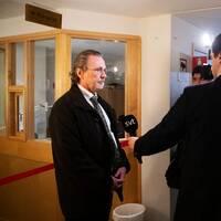 Man i svart kappa intervjuas av journalister.
