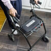 En bild på en äldre kvinna som går med en rullator.