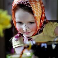 En person som målar påskägg och en flicka utklädd till påskkärring som häller upp påskmust.