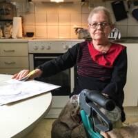 Rose-Marie Nordlund sitter vid köksbordet med en rullator framför sig.