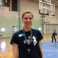 """Elisabeth Egnell har en t-shirt som det står """"girlscamp"""" på och ler mot kameran. I bakgrunden tränar några av deltagarna i girlscamp."""