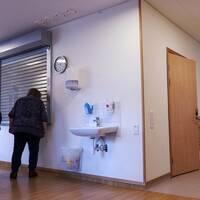En bild på ett slutet kök, där en kvinna tittar in genom en gallerliknande jalusi som är fördragen för en lucka in till köket.