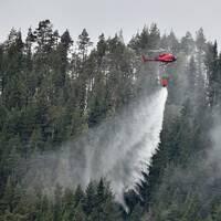 En helikopter släcker en skogsbrand