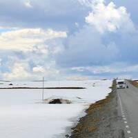 en väg i trädlös fjällmiljö med tunt snötäcke på sidorna