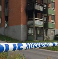 Polisens avspärrningsband i förgrunden. I bakgrunden syns ett brandskadat lägenhetshus.