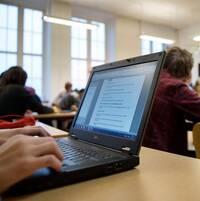 Elever i en skolsal, varaven med dator.