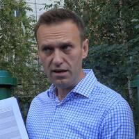 Ryska oppositionsledaren Aleksej Navalnyj och två ryska polisbilar.