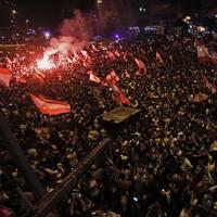Demonstranter vajar flaggor och tänkder bengaleldar i staden Tripoli