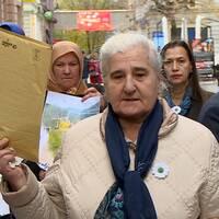 Flera personer står på en gata och protesterar. I mitten en äldre dam som håller upp ett stort kuvert.