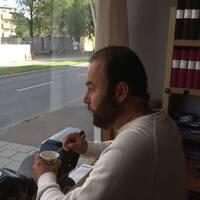 Elias står vid skyltfönstret med kaffet i handen. På andra sidan vägen ser man byggnadsställningar på huset där bomben exploderade.