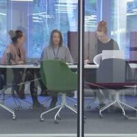 Tre kvinnor sitter vid ett konferensbord. Syns genom glasvägg.