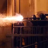Libanesisk kravallpolis skjuter gummikulor mot demonstranter.